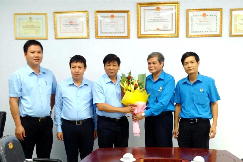 Phó Chủ tịch LĐLĐ Quảng Bình Nguyễn Xuân Toàn tặng hoa, chúc mừng Cty CP Môi trường và Phát triển đô thị Quảng Bình. Ảnh: Lê Phi Long