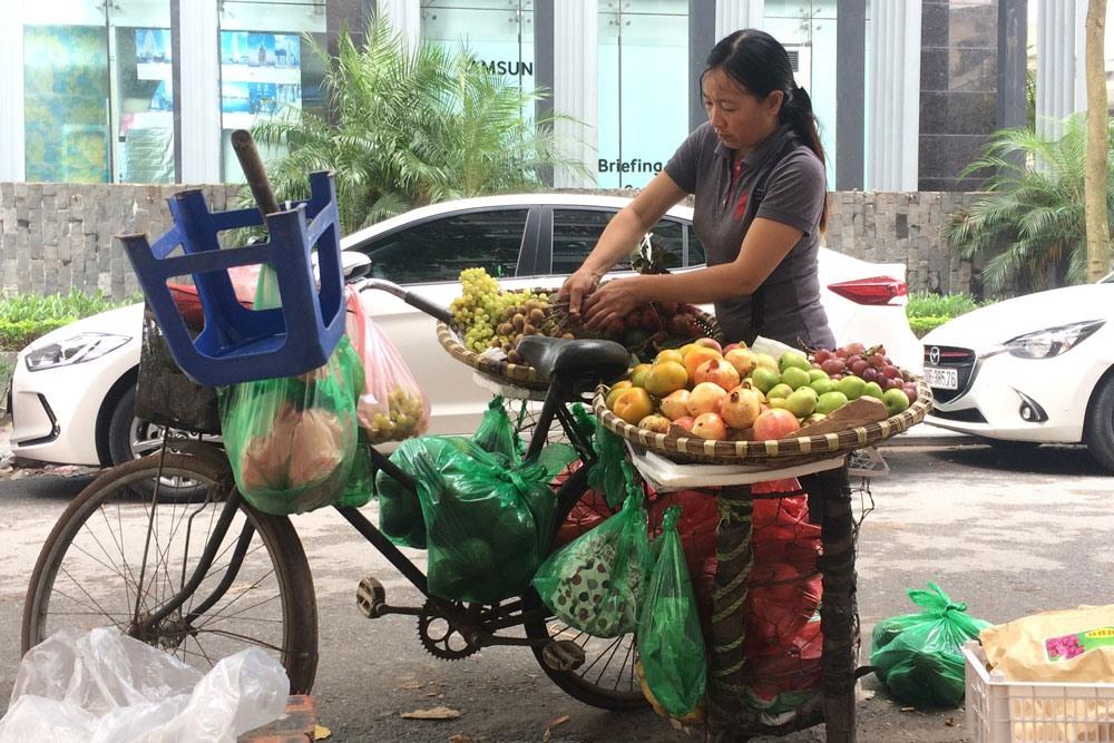 Một phụ nữ đang bán hàng rong trên địa bàn quận Cầu Giấy, Hà Nội. Ảnh: QUẾ CHI