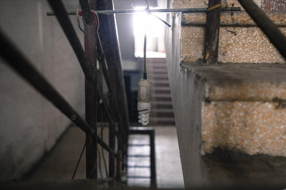 Tầng 1 vừa là nơi tập kết vật liệu thi công của các đơn vị tiến hành thi công cạnh khu đô thị, vừa là nơi tạm trú của một vài người thợ làm việc gần đó. Họ phải dùng một ổ điện dài để nối được chiếc bóng đèn này ra phía cầu thang để chiếu sáng vào ban đêm.