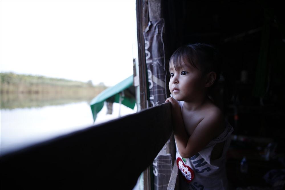 Có những lúc Tít thích ngồi bên cửa sổ, hướng mắt nhìn về phía đô thị sáng đèn và nhộn nhịp, nơi đối lập với xóm Phao mà em đang sống. Phải chăng tiếng vọng lại của còi xe bên kia sông khiến cô bé 2 tuổi tò mò?Đôi mắt vô tư của Tít dường như chưa trông thấy được những khó khăn của bố mẹ, của người dân trong xóm hay cả những ngày dài phía sau sẽ tới. Liệu tương lai của gia đình Tít có tươi sáng và rộng mở được như đôi mắt của em, chẳng ai có thể biết được.