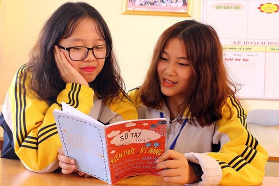 Lý Phương Anh và Trần Lê Linh Chi (lớp 12, Trường THPT Chuyên Chu Văn An, Lạng Sơn) với cuốn sổ tay trang bị kỹ năng phòng chống tội phạm mua bán người cho lứa tuổi học sinh. Ảnh: NVCC