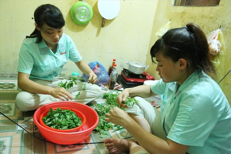 Công nhân Văn Thị Thu Thảo và Lèng Thị Phượng chuẩn bị bữa ăn tối với rau và một ít thịt lợn. Ảnh: HẢI NGUYỄN