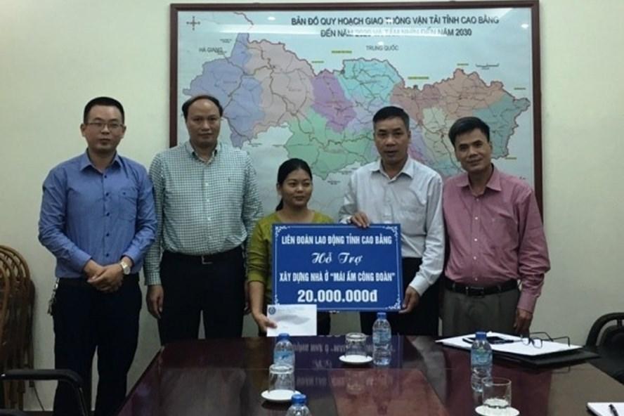 Đồng chí Hoàng Văn Thông - Phó Chủ tịch LĐLĐ tỉnh - trao tặng tiền hỗ trợ cho đoàn viên Hứa Thị Thắm sửa chữa nhà ở. Ảnh: Trần Sơn.
