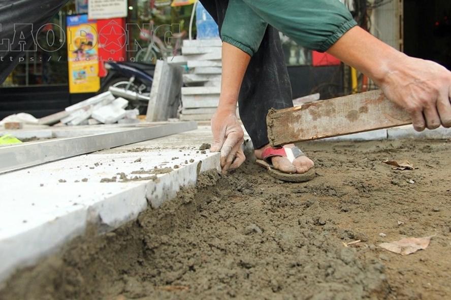 Nhiều đoạn vỉa hè đã gỡ lớp bề mặt cũ, sẵn sàng cho việc thi công lát vật liệu mới. Trong ảnh công nhân dùng đầu búa gõ nhẹ để viên đá kết dính chặt với xi măng, vữa.