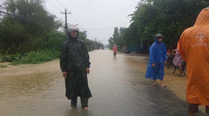 Tuyến đường qua thôn Nông Sơn xã Điện Phước bị nước lũ chia cắt. Chính quyền địa phương cử người túc trực hướng dẫn giao thông. Ảnh: LP