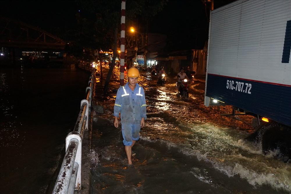 Một công nhân bì bõm dò đường đi trên đường Trần Xuân Soạn (Q.7).