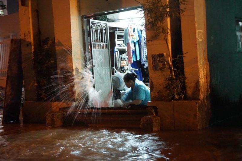 Người dân trên đường Nguyễn Văn Hưởng hì hục tát nước ngập trong nhà ra đường.