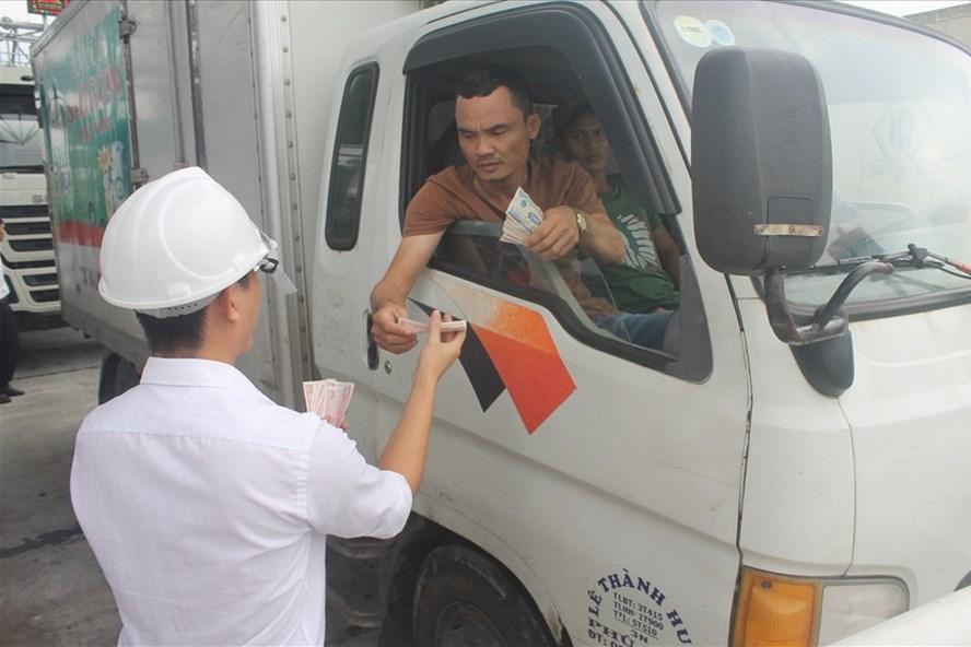 Tài xế này đưa một lốc tiền lẻ, mệnh giá 500 đồng cho nhân viên trạm BOT Ninh An đếm. Ảnh: Nhiệt Băng