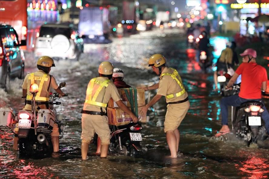 Sự xuất hiện, hỗ trợ của lực lượng CSGT TPHCM khiến người dân rất vui mừng, an tâm hơn khi lưu thông qua những đoạn đường bị ngập trong mùa mưa năm nay. Ảnh: Trường Sơn