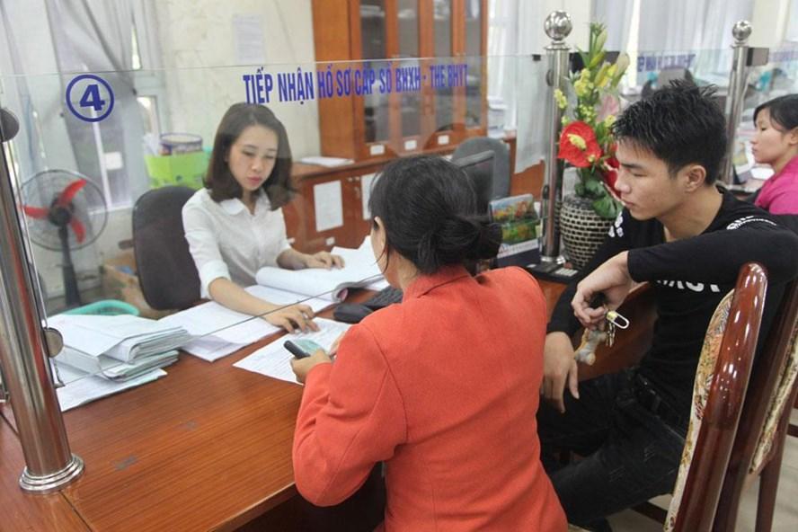 Cán bộ BHXH tiếp nhận hồ sơ cấp sổ bảo hiểm xã hội và bảo hiểm y tế cho người dân. Ảnh: H.A