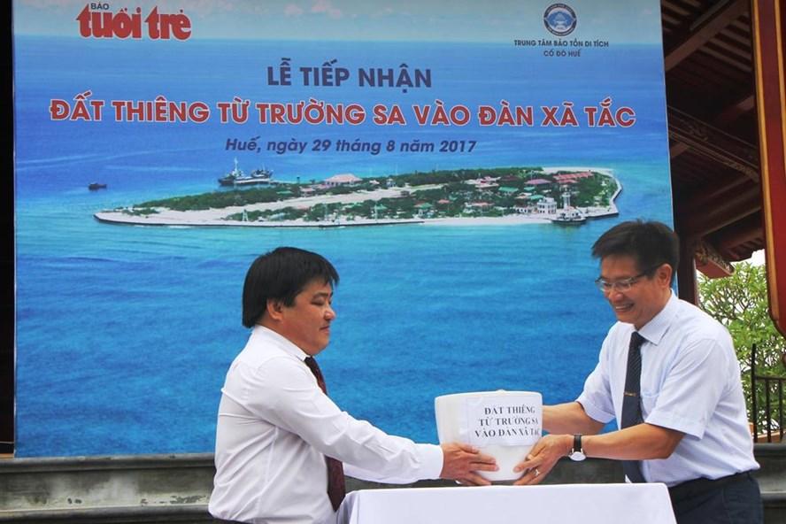 Ông Phan Thanh Hải-Giám đốc Trung tâm Bảo tồn Di tích Cố đô Huế (bên phải) tiếp nhận đất Trường Sa từ lãnh đạo báo Tuổi Trẻ. Ảnh: NĐT