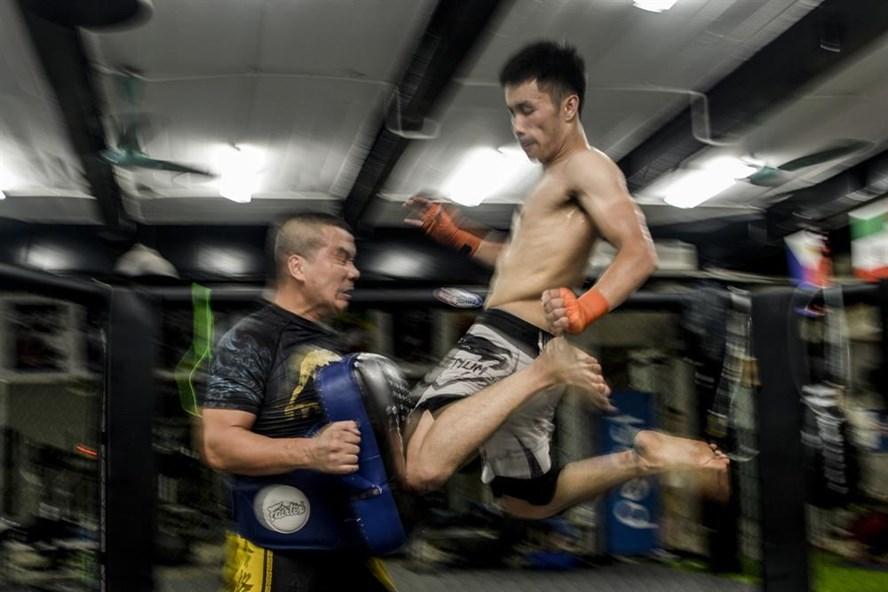 """Võ sư Mai Thanh Ba (trái) đang huấn luyện kỹ thuật """"Gối bay"""", một đòn hiểm của môn phái Muay Thai. Võ sư cho biết, MMA không phải là môn phái võ, MMA chỉ là một bộ luật thi đấu. Để có thể thi đấu tốt trong luật MMA, các võ sĩ phải hội tụ các kỹ năng tổng hợp của nhiều môn phái khác nhau."""
