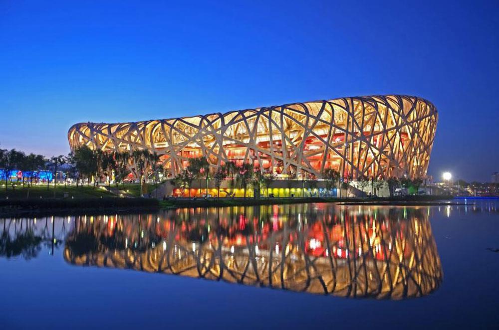 """Sân vận động Bắc Kinh (Trung Quốc): Cũng gọi là """"Tổ chim"""". Hình dáng chiếc tổ chim thể hiện sự vững chãi và độc đáo. Cách """"đan, thắt"""" những vật liệu kết cấu như cách đan một chiếc giỏ mây cùng với sự cố vấn nghệ thuật của nghệ sĩ Ngải Vị Vị, các kiến trúc sư phương Tây này đã thổi hồn vào sân vận động khiến nó uyển chuyển và mềm mại."""