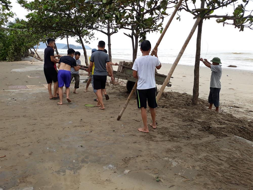 Nhiều người dân xúc cát đổ ra biển (ảnh D.N)