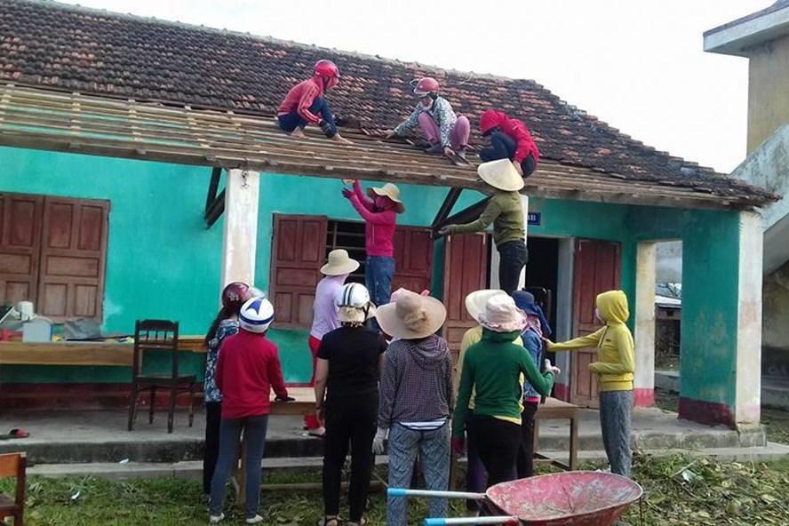 Cảm động cô giáo leo mái nhà, lợp ngói trường học sau bão số 10 - ảnh 1