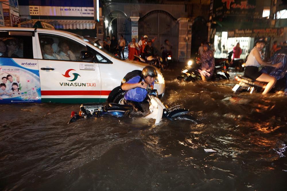 Hàng chục người chạy xe máy ngã nhào khi có ôtô chạy ngang qua tạo thành sóng.