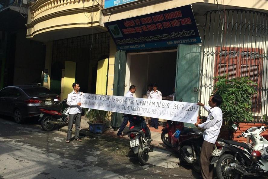 Người lao động căng băng rôn đòi lương trước cửa Cty bảo vệ TSG. Ảnh: Quế Chi