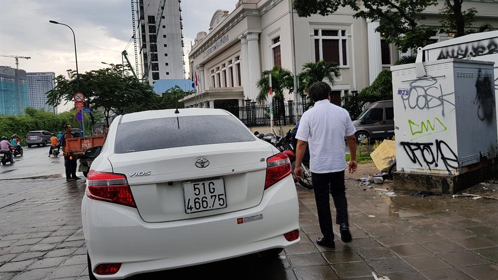 """Ông Hải yêu cầu xử lý 3 chiếc xe được cho là đậu trên vỉa hè đường Võ Văn Kiệt mặc cho các tài xế này nói là """"phải có tình có lý"""". Ảnh: Trường Sơn"""