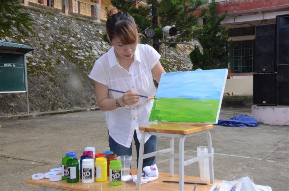 Học sĩ Trịnh Huyền hướng dẫn học sinh vẽ tranh trên vải. Ảnh: HH