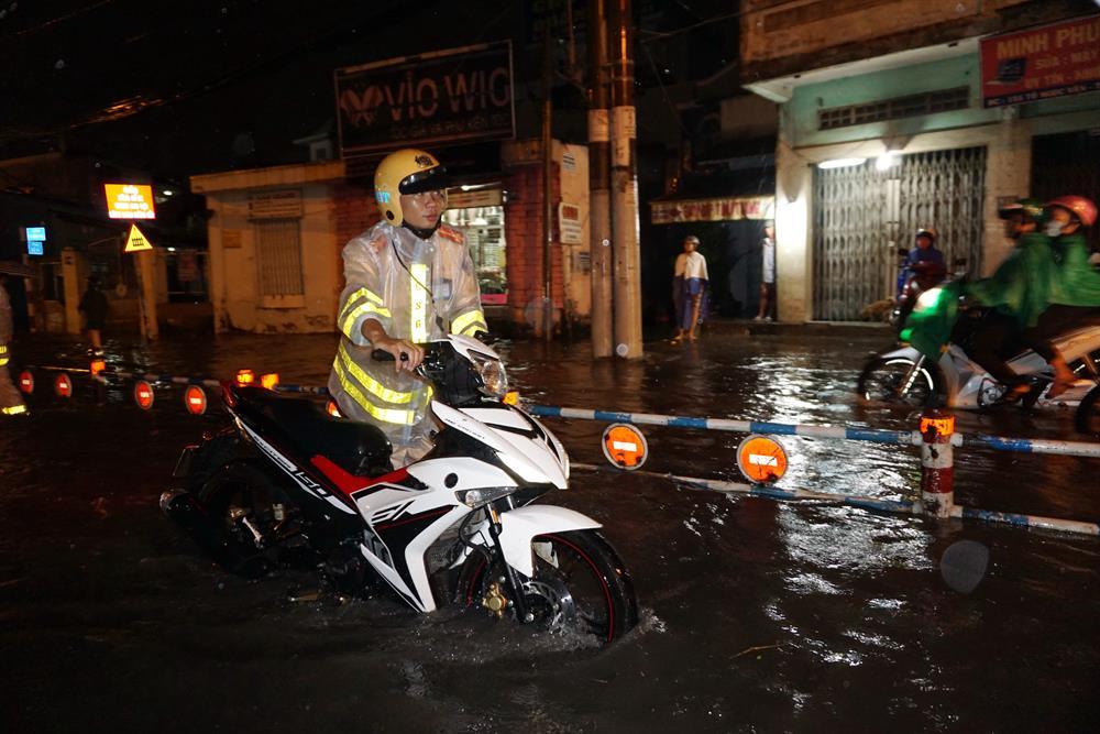 CSGT đẩy xe chết máy cho người dân qua đường ngập.  Ảnh: M.Q