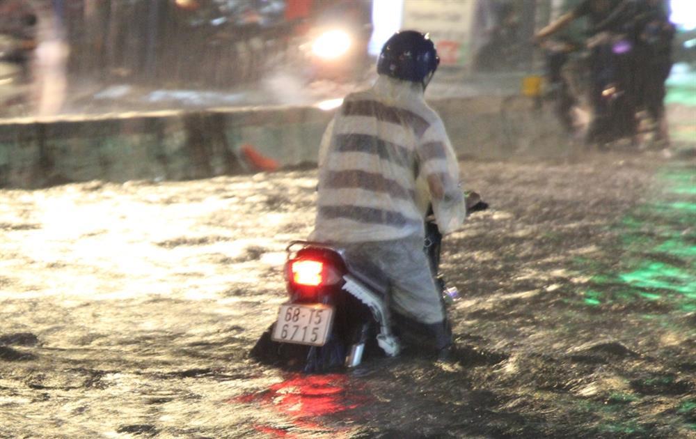 Nhiều người dân lâm cảnh lội bì bóm với chiếc xe máy của mình khi đường Huỳnh Tấn Phát ngập suốt 4km trong hàng giờ đồng hồ. Ảnh: Trường Sơn