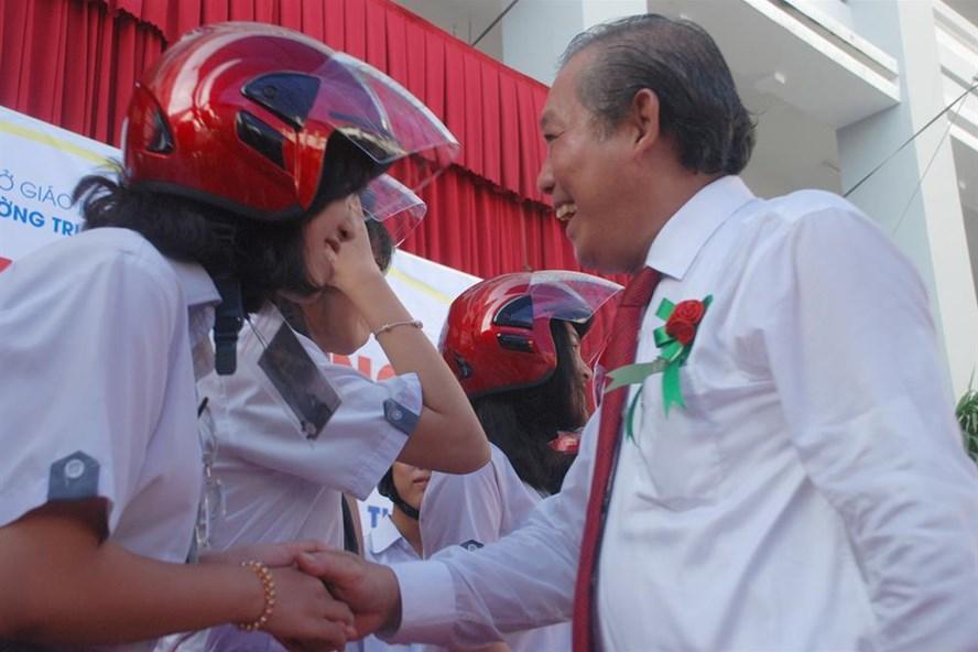 Phó Thủ tướng Thường trực Trương Hòa Bình đội mũ bảo hiểm cho các em học sinh trường THPT Võ Văn Kiệt (ảnh T.H)