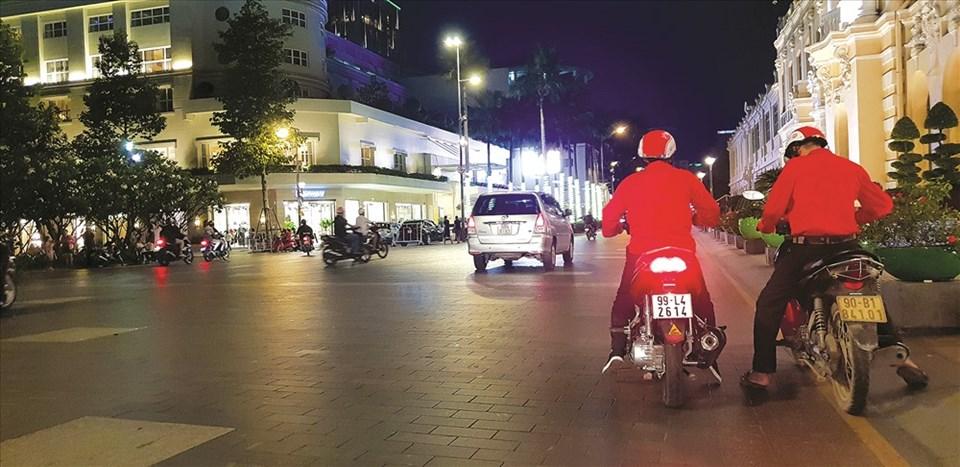"""Sài Gòn luôn luôn có chỗ cho những người chăm chỉ. Trong ảnh là những lao động nhập cư chạy """"xe ôm công nghệ"""" trên đường Lê Thánh Tôn, quận 1. Ảnh: Trần Nam Luân"""