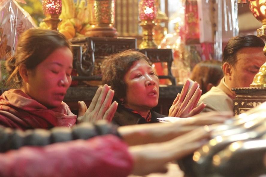 Nhiều người dân cố gắng sờ vào chân tượng lấy may. Ảnh: Trần Vương