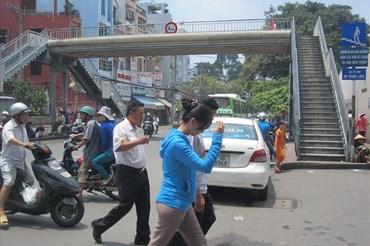 Trước cổng BV Ung Bướu (Q.Bình Thạnh), mặc dù có cầu vượt bộ hành nhưng người dân vẫn đi bộ qua đường. Ảnh: M.Q
