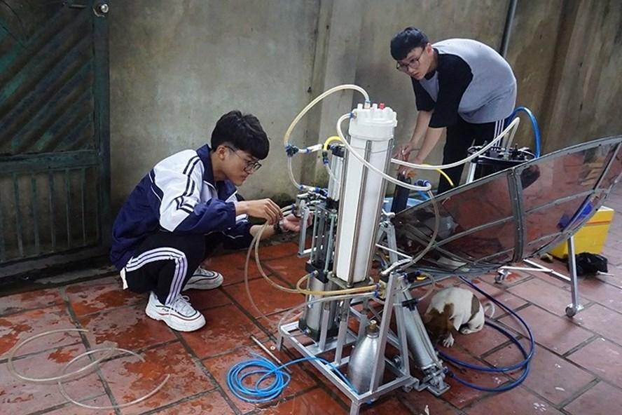 """Em Nhật Anh (trái) và Văn Long đang kiểm tra dự án thiết bị """"hô biến"""" nước mặn thành nước ngọt bằng năng lượng sóng biển. Ảnh: NA"""