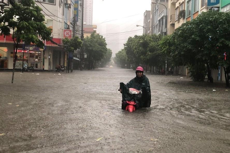 Người dân mướt mải dắt xe, lội phố ngập sâu.