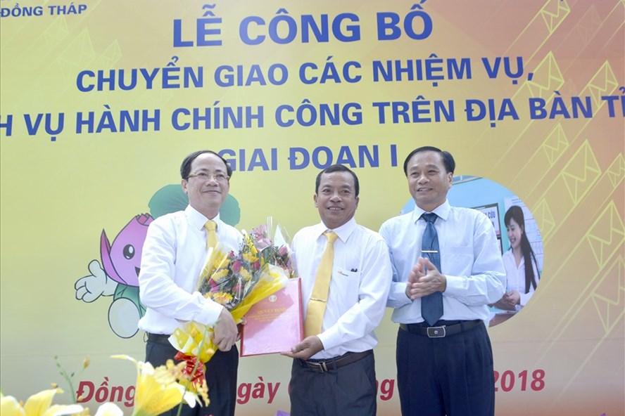 Ông Nguyễn Văn Dương (phải) cùng ông Phạm Anh Tuấn tặng hoa cho đại diện Bưu điện Đồng Tháp trong lễ công bố. Ảnh: Lâm Lý