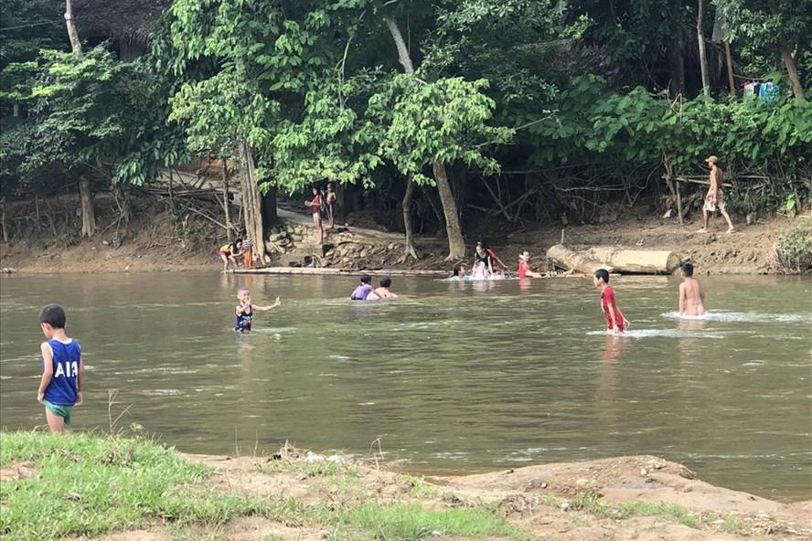 Những đứa trẻ ở xóm Chiềng 3 vẫn hồn nhiên nô đùa dưới dòng suối Chiềng trong buổi chiều u ám Ảnh: Thành Trung