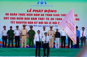 Phó Chủ tịch UBND TPHCM Trần Vĩnh Tuyến trao cờ phát động ra quân thực hiện năm An toàn giao thông 2019. Ảnh: M.Q