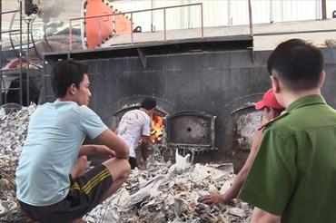 Công nhân đổ rác thải công nghiệp vào lò đốt của công ty sản xuất giấy.