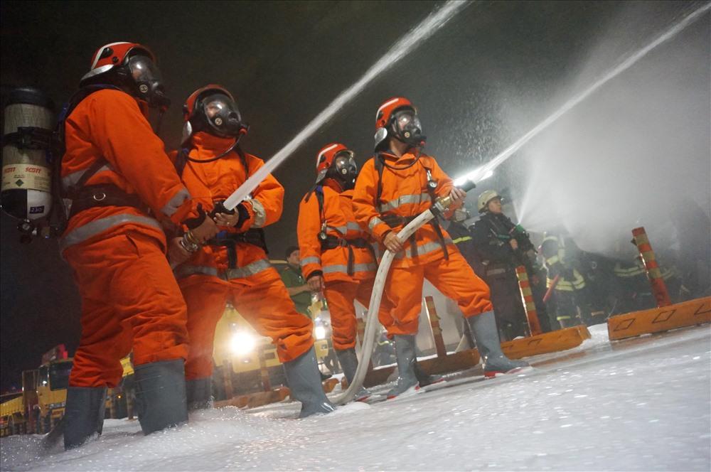Lính cứu hỏa căng thẳng phun nước để dập lửa.