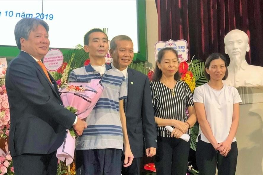 Giám đốc Bệnh viện Việt Đức tặng hoa chúc mừng bệnh nhân và gia đình. Ảnh: T.L