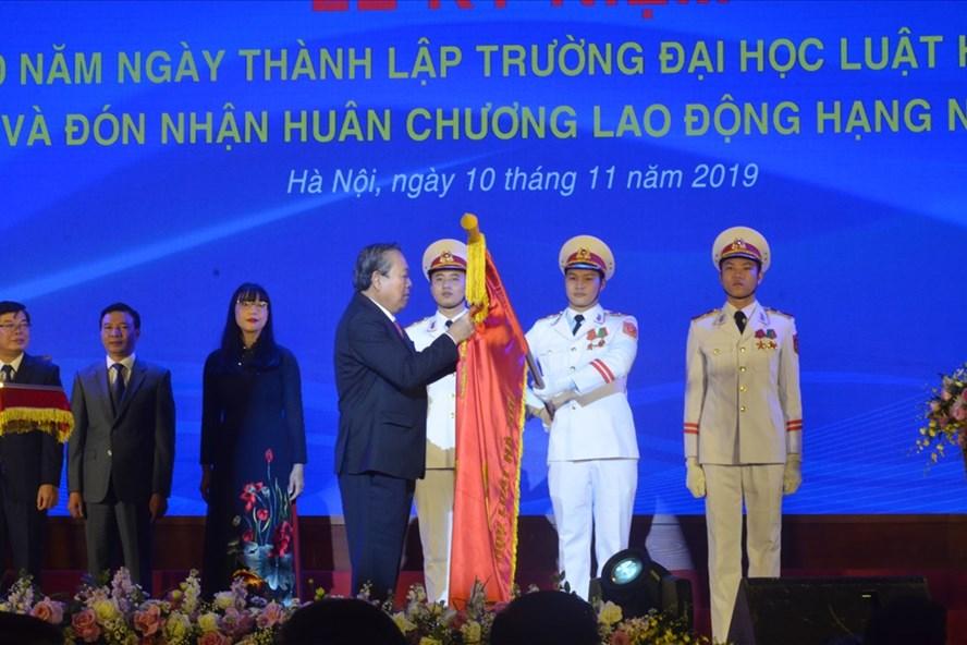 Phó Thủ tướng Thường trực Chính phủ Trương Hòa Bình gắn Huân chương Lao động hạng Nhất lên lá cờ truyền thống của trường tại lễ kỷ niệm.