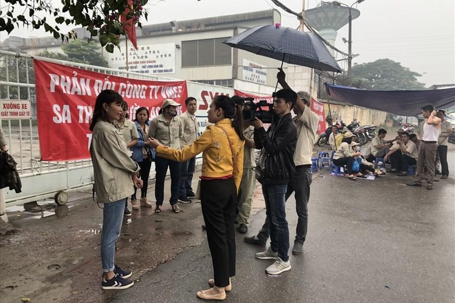 Công nhân Cty VMEP đội mưa phản ánh vụ việc với phóng viên Báo Lao Động. Ảnh: V.L