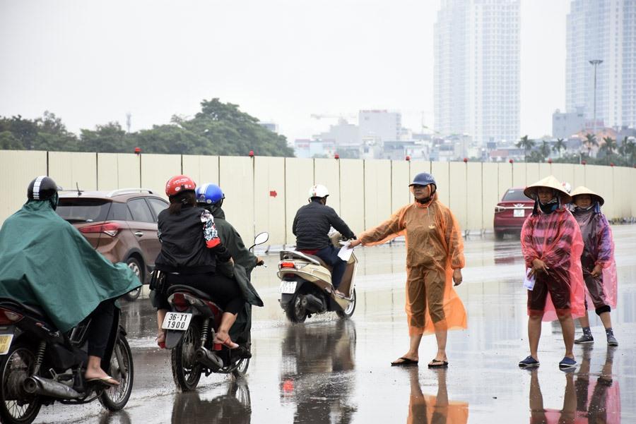 Bất chấp trời mưa, nguy hiểm, các phe vé vẫn đứng ra đường chính để mời chào