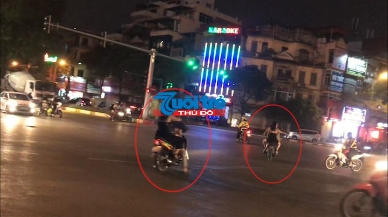 """Các thanh niên đầu trần lái xe máy chở theo các cô gái """"tay vịn'' chạy ngược chiều, vượt đèn đỏi, vi phạm Luật Giao thông đường bộ."""