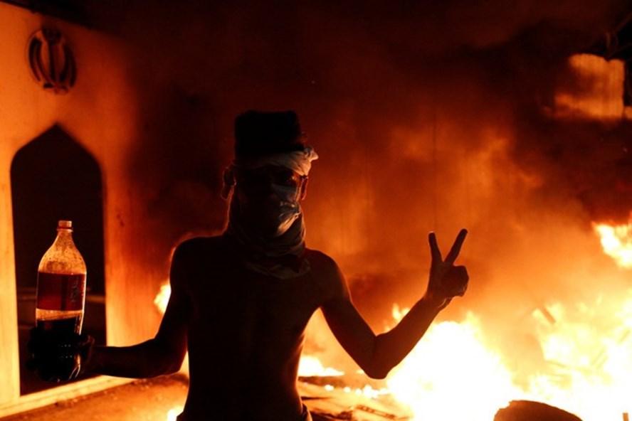 Một người biểu tình Iraq trước lãnh sự quán Iran đang cháy. Ảnh: Reuters