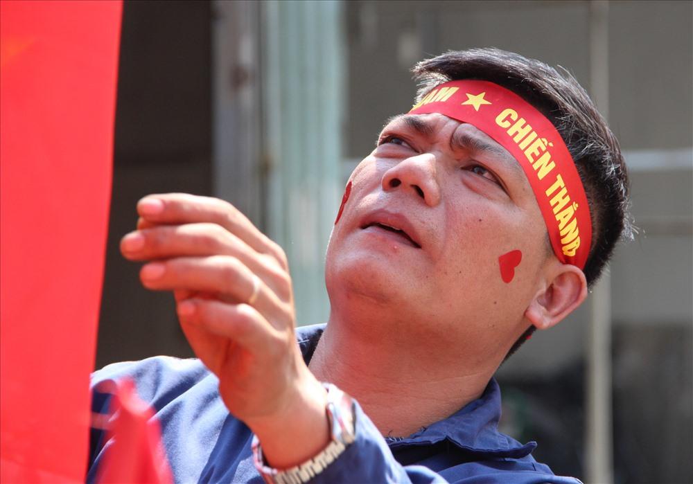 Trên đường ĐT 743 anh Lê Anh Hựu đang sửa soạn cờ để bán cho người lao động cổ vũ bóng đá. Ảnh: Đình Trọng.