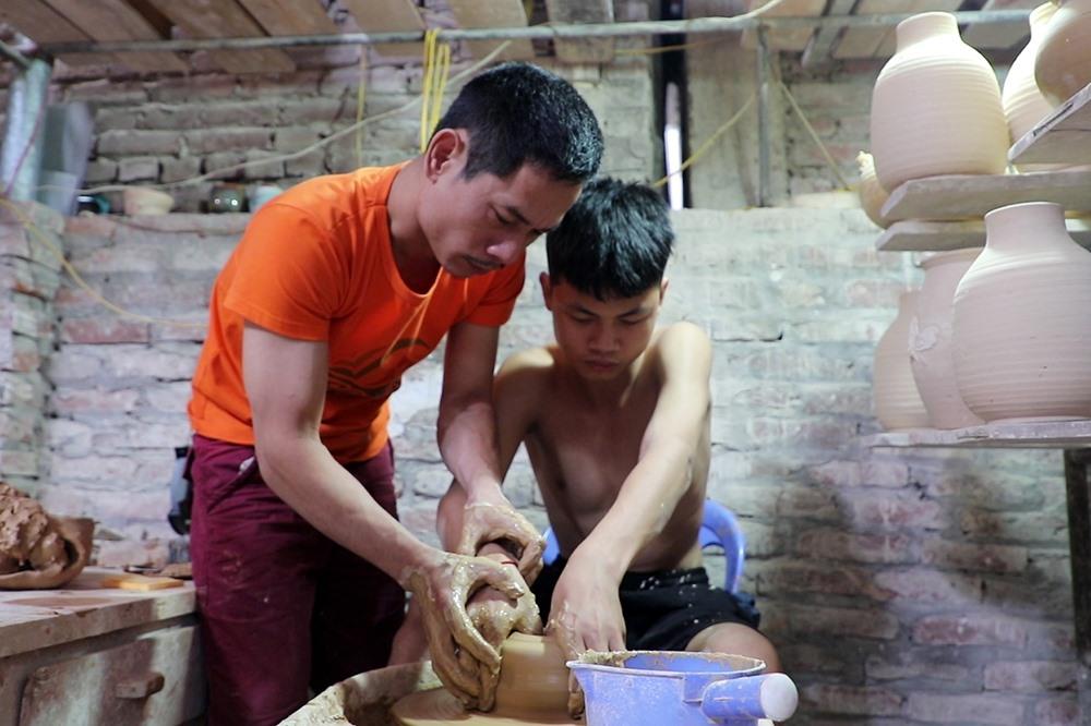 """Giờ đây ngồi cạnh bố bên chiếc bàn xoay, cậu con trai Phạm Duy Anh 17 tuổi cũng đã tập tành nghề gốm như ngày xưa anh Đạo học nghề của bố. """"Nó học được nghề gốm của cha ông cũng tốt thôi, nhưng vất vả và nghèo lắm"""", anh nói."""