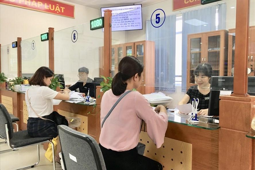 Cán bộ BHXH TP.Hà Nội hướng dẫn người dân hoàn thiện hồ sơ BHXH.  Ảnh: Hà Nguyên