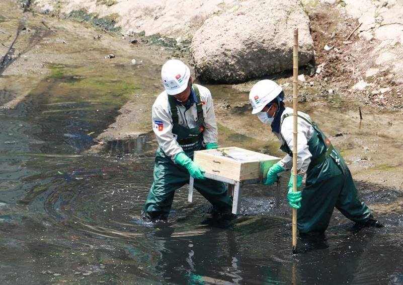 Công nhân lắp tấm Bioreactor xuống khu vực thí điểm làm sạch một đoạn sông Tô Lịch. Ảnh: PV