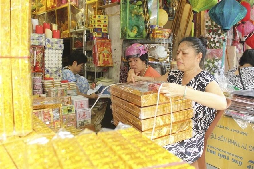 Một tiểu thương tại phố Hàng Mã gói đồ cho khách hàng. Ảnh Trần Vương