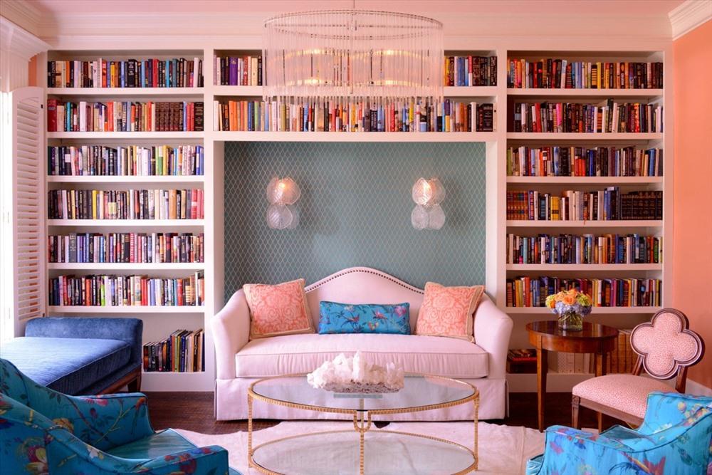 Một phòng khách chủ đạo là màu hồng phấn, được tô điểm bởi hai chiếc ghế sofa xanh biển tươi tắn và rất nhiều sách xếp ngay ngắn trên kệ.