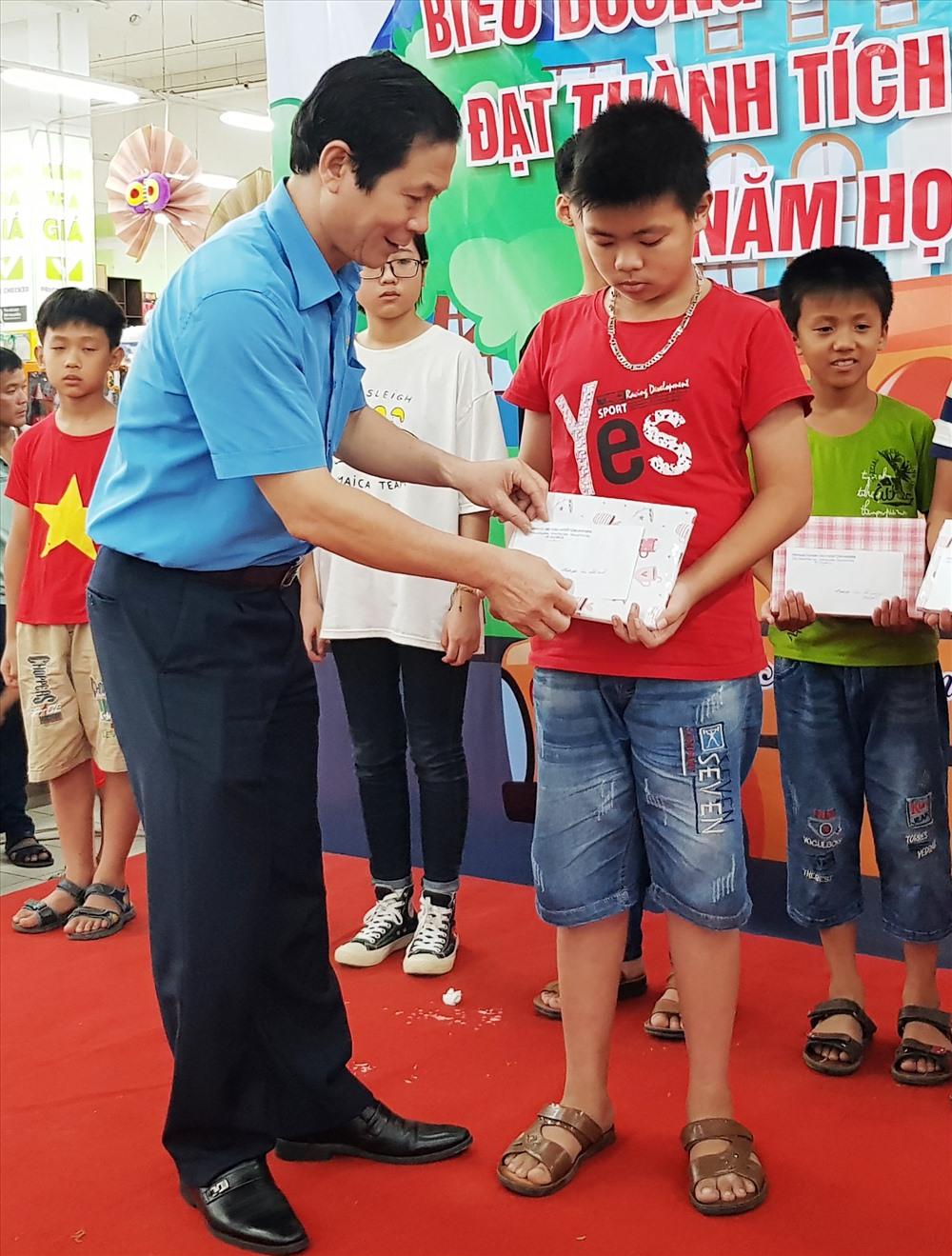 Đồng chí Trần Kim Long, Phó chủ tịch LĐLĐ tỉnh Ninh Bình tặng quà cho các em học sinh. Ảnh: NT