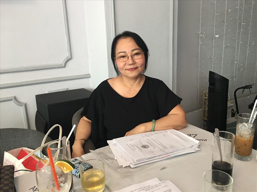 Bà Lê Thị Ham bên hồ sơ khiếu kiện dấu hiệu giả chữ ký. Ảnh: C.H